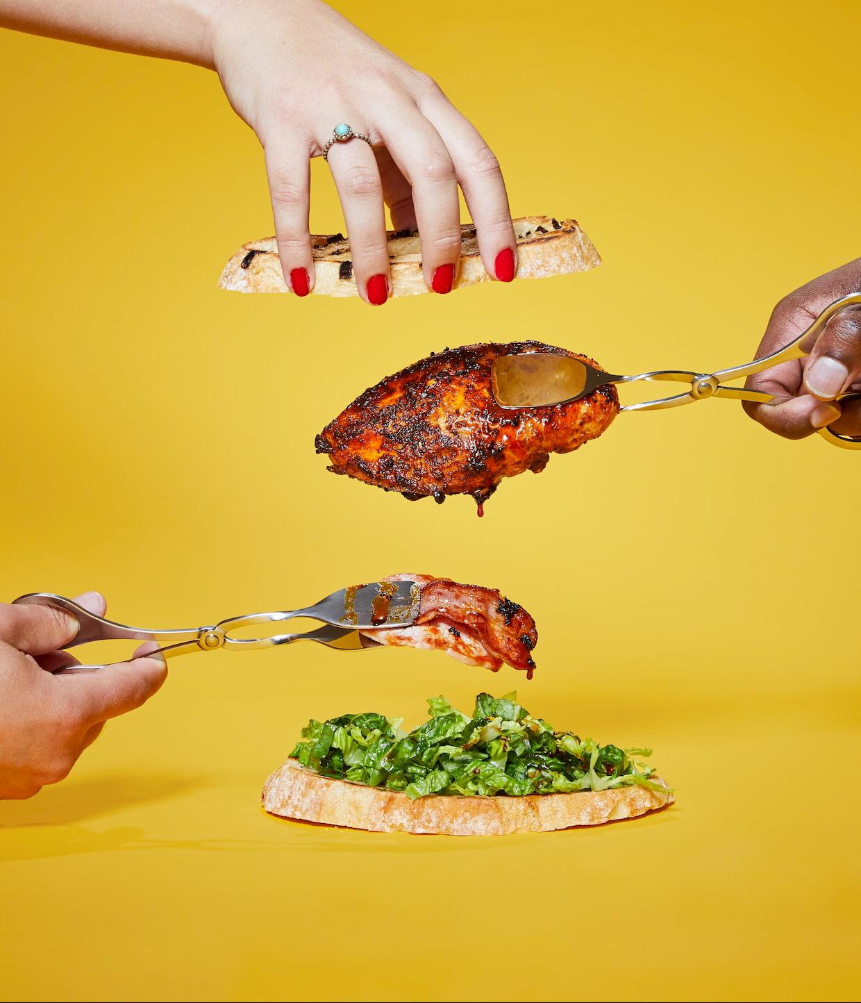 Marinated chicken sandwich being assembled