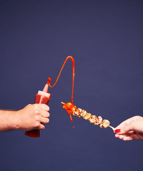 Sauce being squirted onto food on a skewer